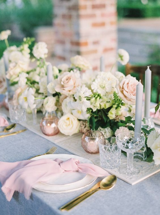 a sophisticated spring wedding tablescape with a blue tablecloth and pink napkins, neutral and blush blooms and grey candles