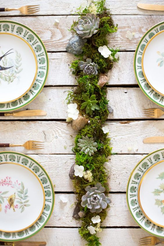 a stylish wedding centerpiece of moss, white blooms and pale succulents in the center is a cute rustic and all-natural idea