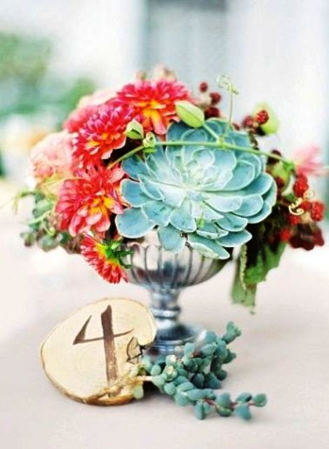 a summer wedding centerpiece with a silver bowl, bright blooms and a large succulent plus a wooden slice table number