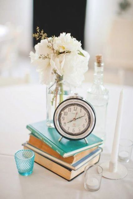 a sweet and airy wedding centerpiece of a stack of books, candles, white blooms and a vintage clock on top