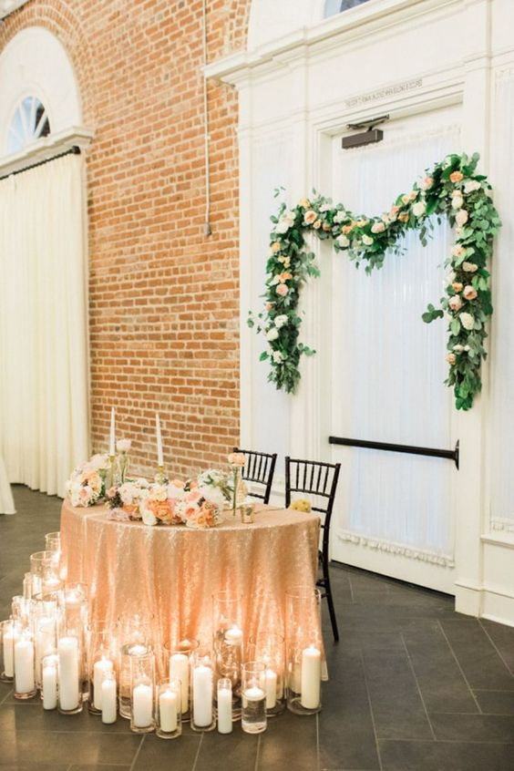 a sweetheart table covered with a gold sequin tablecloth, pastel florals and surrounded with candles