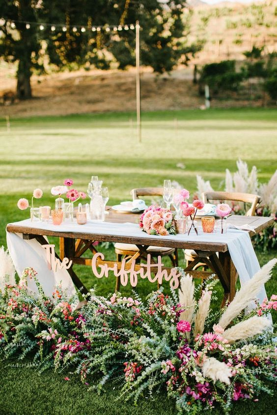 a sweetheart table decorated with greenery, blooms and dried herbs plus candles and florals and a calligraphy sign
