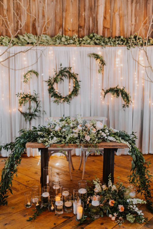 a sweetheart table with a lush greenery and pastel bloom table runner, lots of floating candles and wreaths with lights behind
