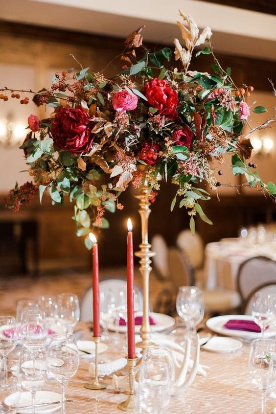 a tall wedding centerpiece with much texture, greenery, deep red and pink blooms and pink candles in gold candleholders