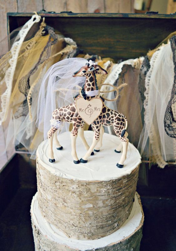 a textural bark wedding cake with giraffe toppers and a heart for a safari wedding