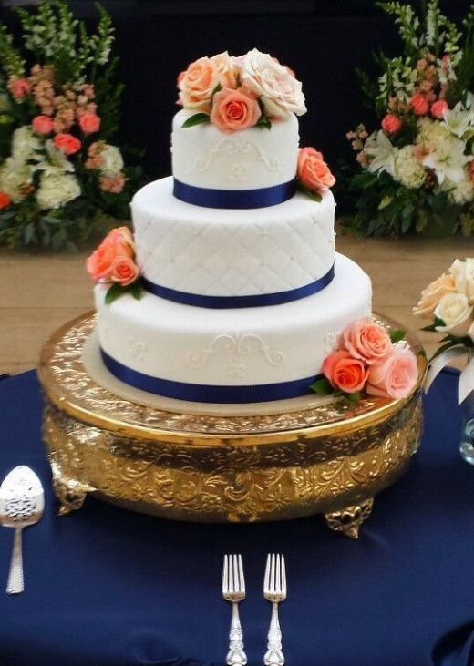 a textural white wedding cake with navy ribbons and coral and blush blooms for decor