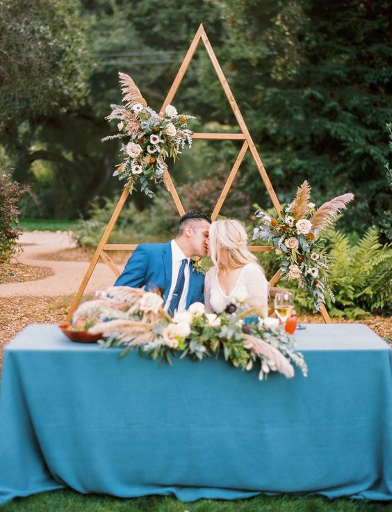 a triangle wedding arch with lush greenery, florals can be a nice accent for the sweetheart table