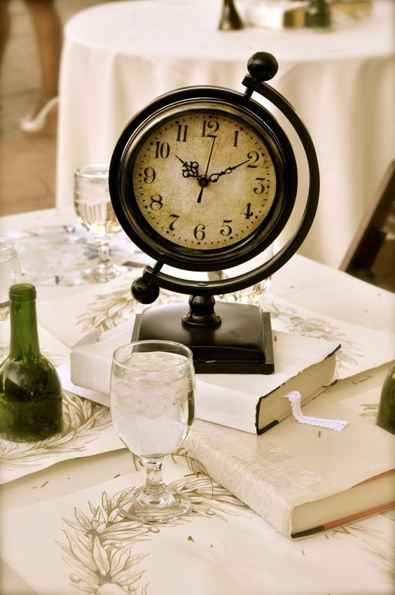 a vintage wedding centerpiece with a stack of books and a large vintage clock is a creative ide