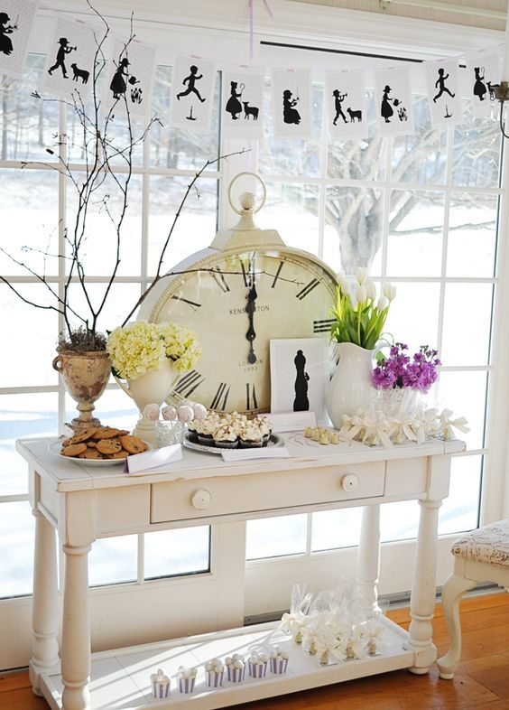 a vintage wedding sweets table with bright and white blooms and an oversized clock for decor