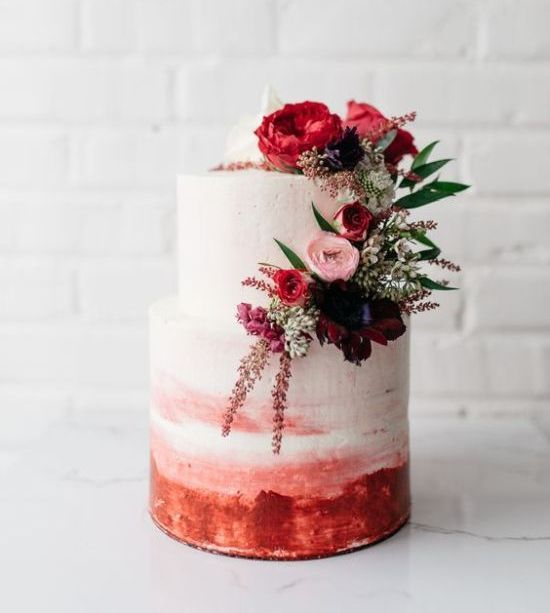 a watercolor wedding cake in pink and red, with burgundy, pink and red blooms and greenery