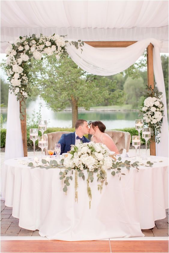 a wedding arch placed right behind the sweetheart table, lush neutral florals and greenery to mark the sweethearts