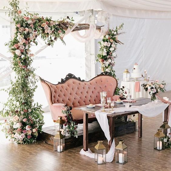 a wedding arch with lush greenery, pink blooms and fabric plus candle lanterns on the floor