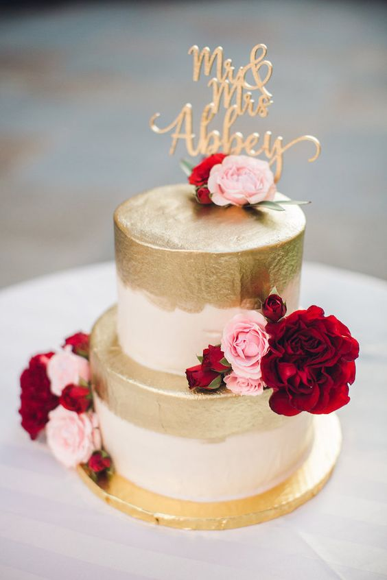 a wedding cake with gold leaf, pink and deep red blooms and a calligraphy gold topper for a glam wedding