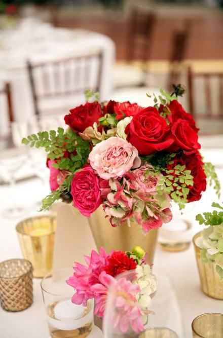 a wedding centerpiece of a gold bucket, pink and red blooms, greenery and candles plus some green hydrangeas