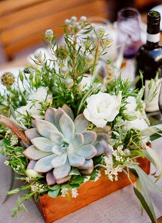 a wedding centerpiece with a wooden box planter, some blooms and berries, greenery and a pale succulent