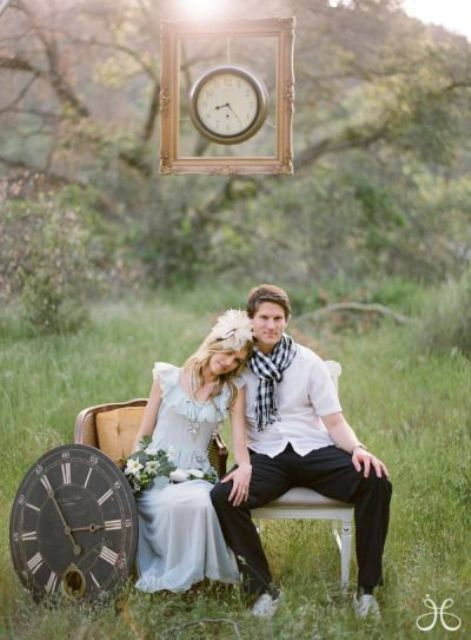 a wedding portrait done with clocks   one hanging over the sofa and another next to it