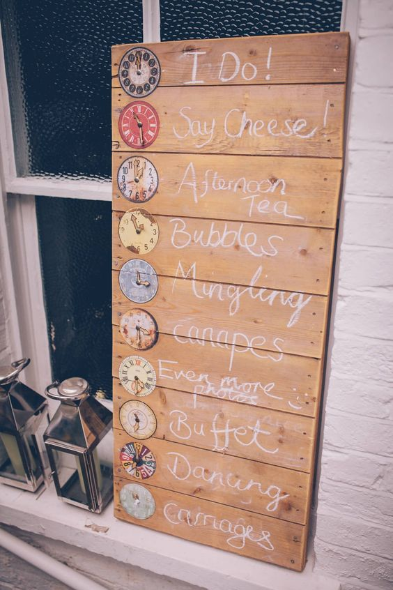 a wedding sign of wood, with colorful clocks that mark each zone of the wedding venue