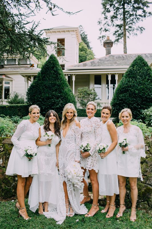 a white mismatched lace bridesmaid dresses and silver shoes for a chic and elegant all white wedding in summer