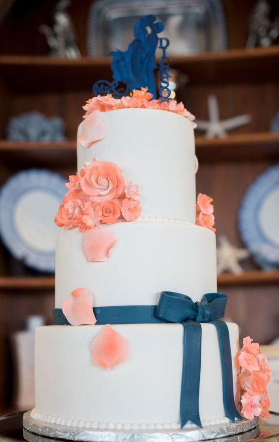 a white wedding cake decorated with coral sugar blooms and petals, a navy ribbon and a romantic cake topper