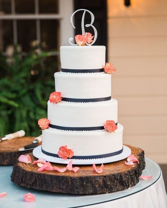 a white wedding cake with navy ribbons, coral blooms and a monogram boutonniere is timeless classics