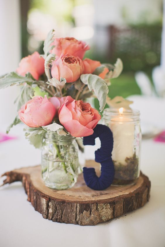 a wooden slice, a navy yarn covered table number, a candle in a jar and corla pink blooms in jars as a cool rustic centerpiece