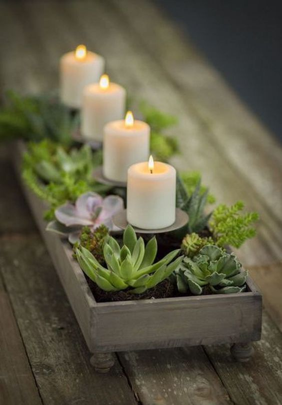 a wooden tray with succulents and greenery plus candles on stands is a cute vintage meets rustic centerpiece