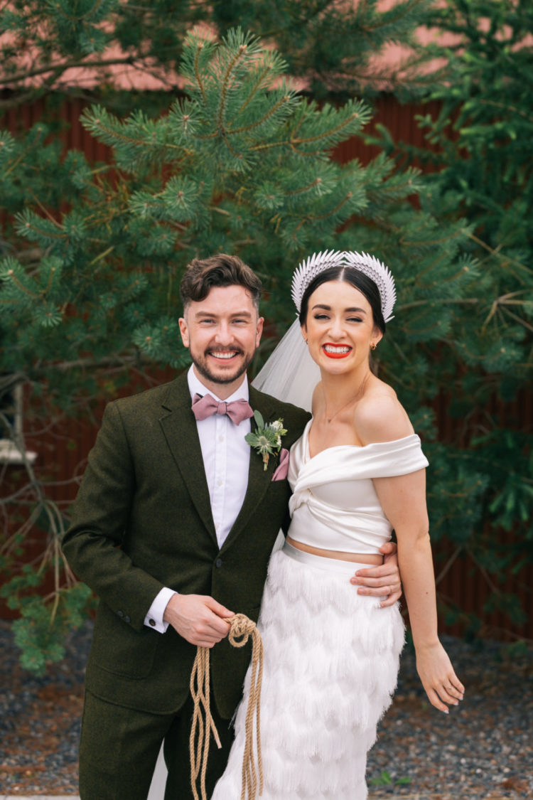 a woolen suit, a white shirt and a dusty pink bow tie and a matching handkerchief for a summer or fall wedding