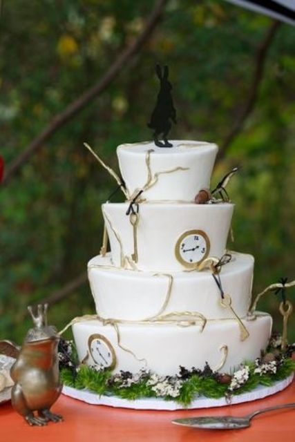 an Alice in Wonderland wedding cake decorated with keys, clocks, greenery and a fun rabbit topper