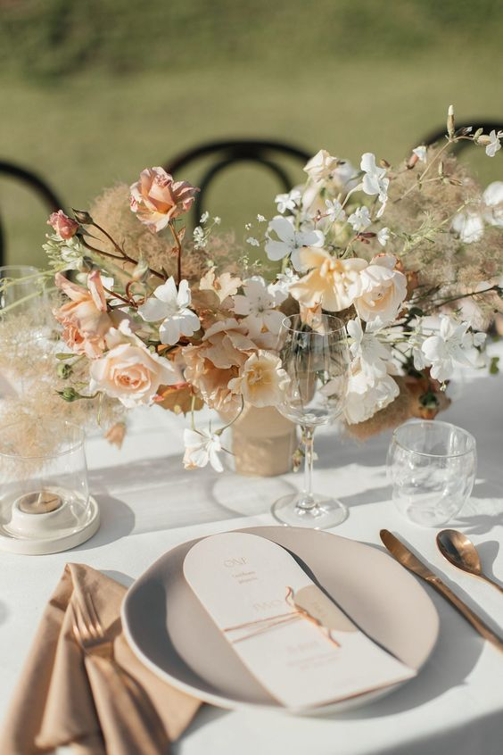 an airy spring wedding tablescape with pastel and white blooms, blush napkins and grey plates, dark cutlery and dried touches