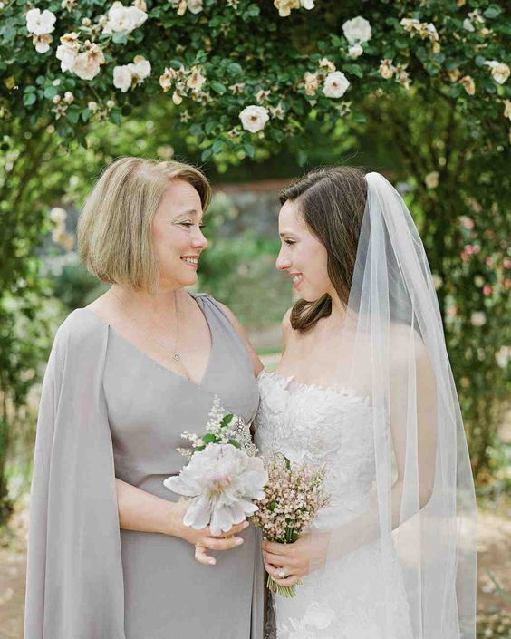 an elegant and simple light grey wrap dress with a deep neckline and a capelet are lovely for a chic mother of the bride look