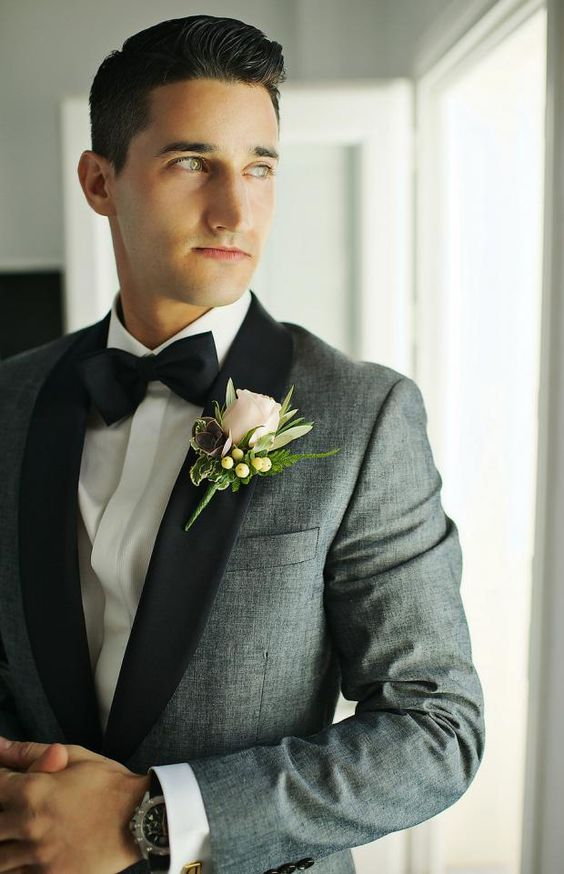 an elegant grey tux with black lapels and a black bow tie plus a neutral floral boutonniere for summer or fall