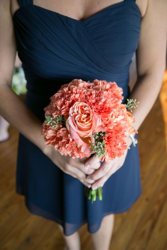 an elegant strapless navy knee bridesmaid dress and a bright coral pink bouquet make up a bright combo