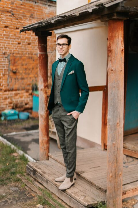 an emerald blazer, a green plaid shirt and a woolen suit with a waistcoat plus tan Chelsea boots