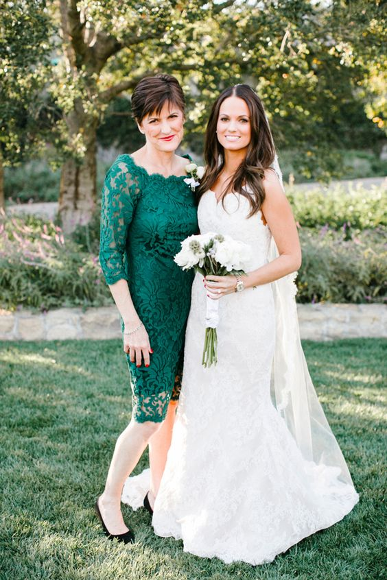 an emerald lace midi fitting dress with a bateau neckline and black shoes are a great combo for a fall wedding