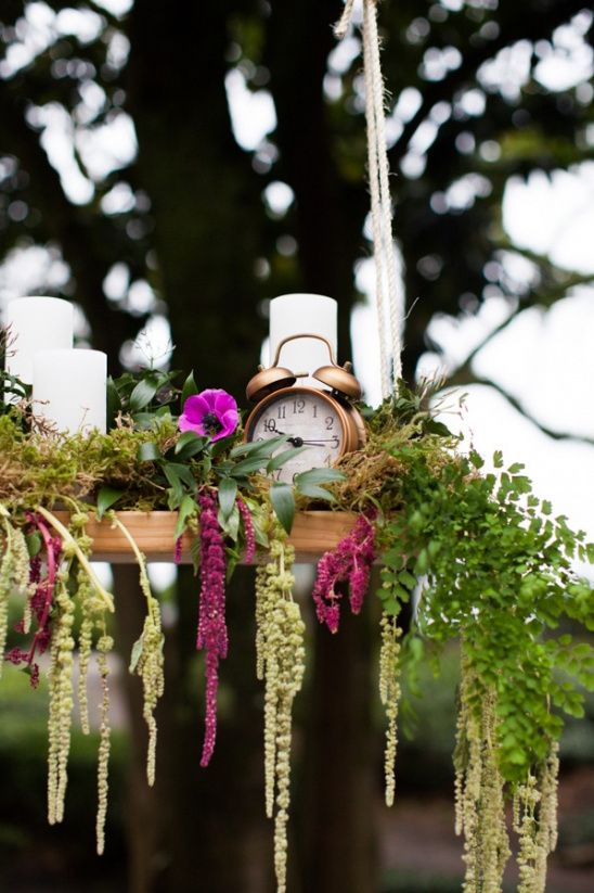 an overhead wedding decoration   a shelf with pillar candle, cascading greenery and pink blooms plus a clock