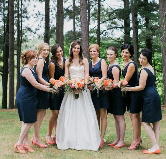 bridesmaids wearing knee navy dresses with thick straps and coral shoes plus updos for an elegant look
