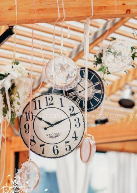 cute wedding decor with lace doilies, cardboard clocks and blooms hanging down from the beams
