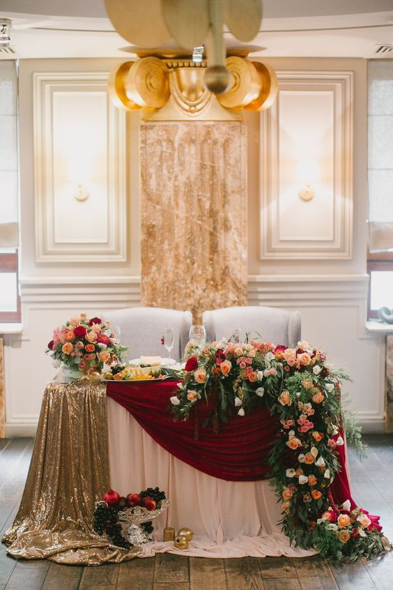 elegant gold and burgundy tablecloths, lush florals and greenery and a glass bowl with fruits