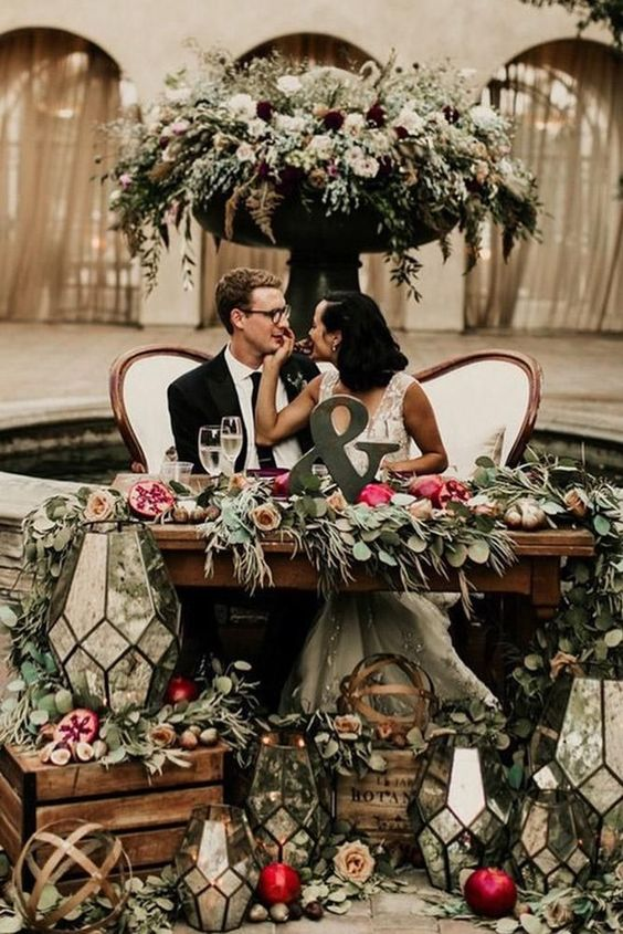 lush greenery, bright and white blooms, pomegranates, candle lanterns and an ampersand for accenting the table