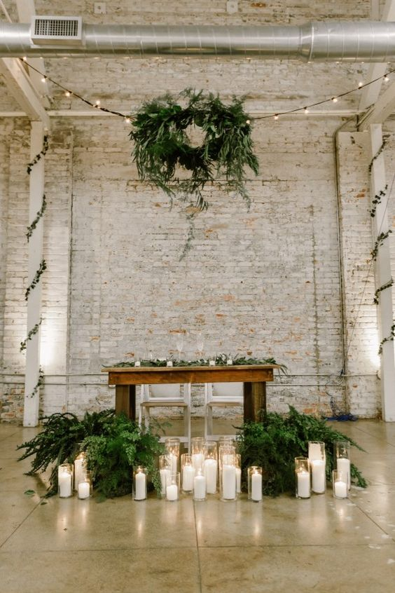 lush potted greenery, lots of candles and a greenery wreath over the table for an industrial wedding