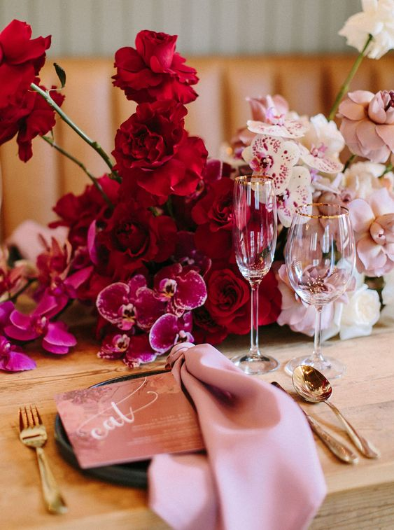 lush table decor with hot pink, red and light pink blooms and pink napkins plus gold cutlery for a luxurious wedding