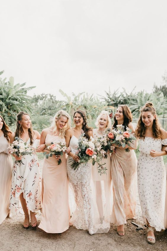 mismatched blush and neutral printed bridesmaid dresses of midi and maxi lengths for a summer wedding