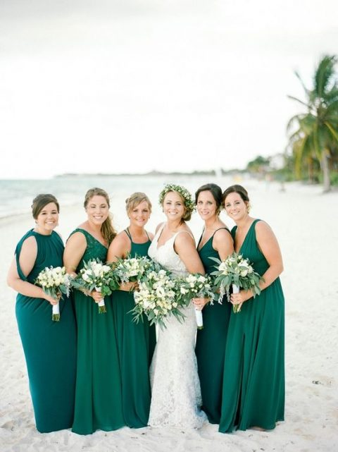 mismatched emerald maxi bridesmaid dresses and a teal one for the maid of honor for a tropical wedding