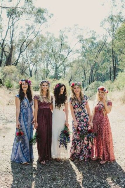 mismatched floral print bridesmaid maxi dresses in bold colors and floral crowns for a boho wedding in summer or fall