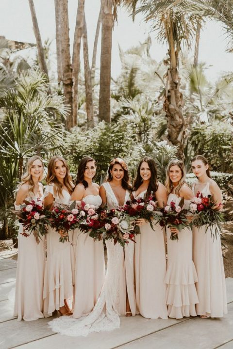 mismatched ivory and blush bridesmaid maxi dresses with ruffles in various places