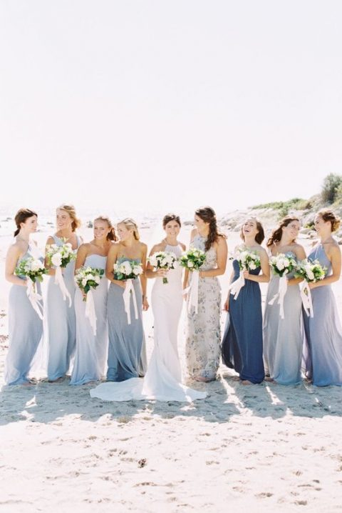 mismatched maxi bridesmaid dresses in blue shades and a floral print one for a coastal wedding