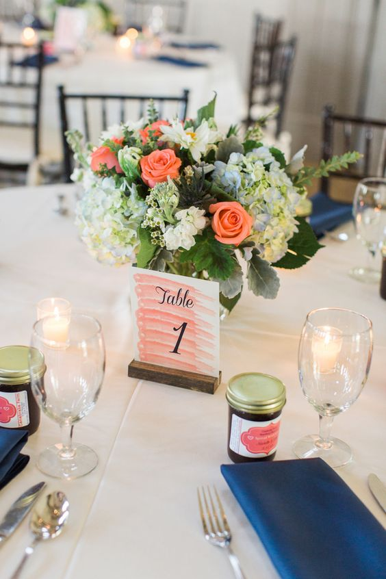 navy napkins, a coral pink table number, a bright floral centerpiece of white, blue and coral blooms for a table setting at the reception