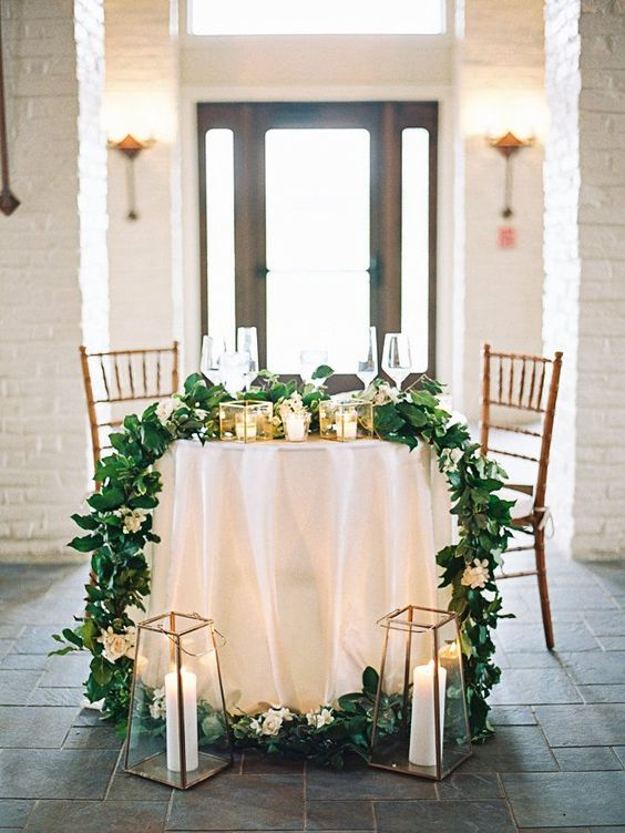 oversized candle lanterns, a greenery and white bloom table runner and some candles on the table