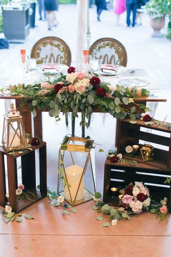 oversized candle lanterns, crates with blooms and greenery and a greenery and floral table runner