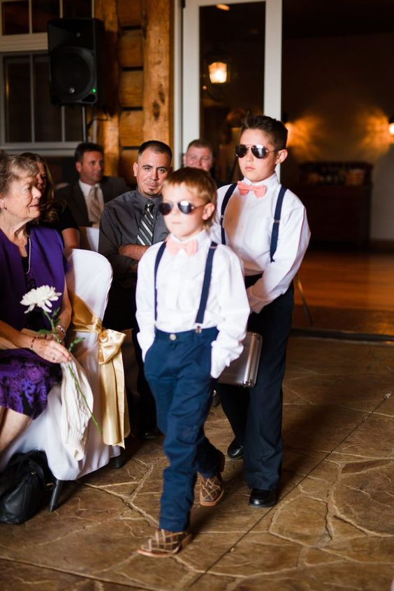 ring bearers rocking navy pants and suspenders, white shirts and coral pink ties for a cool look